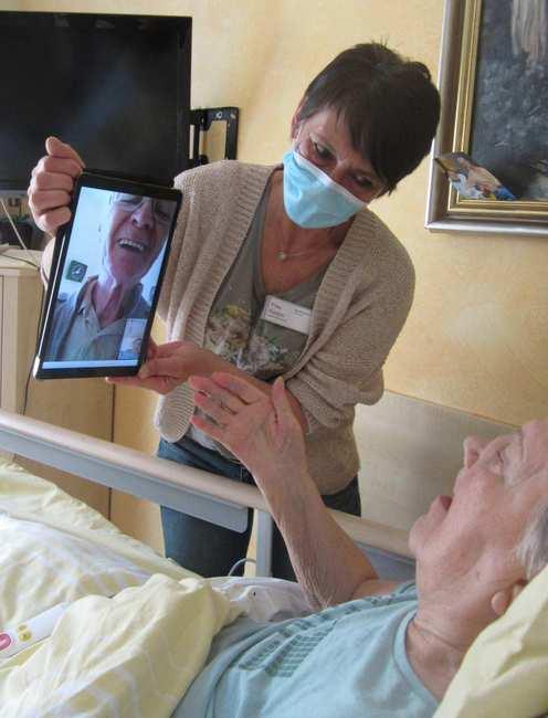 Eine Frau mit Mundschutz hält ein Tablet vor eine alte Dame, die in einem Pflegebett liegt. Auf dem Tablet-Bildschirm lacht ein älterer Herr.
