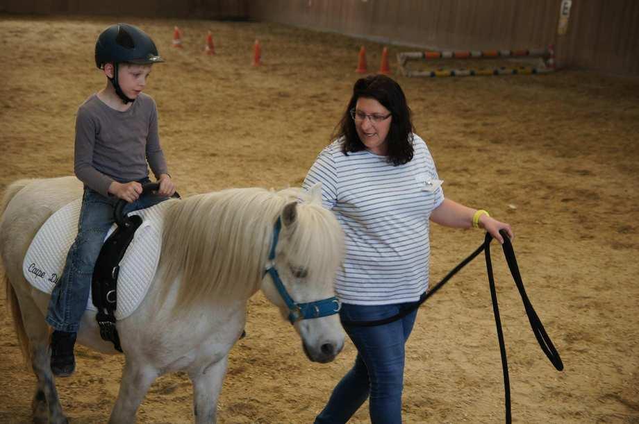Eine Frau führt ein weißes Pony an einer Longe. Ein Junge mit schwarzem Reithelm sitzt auf dem Pferderücken.