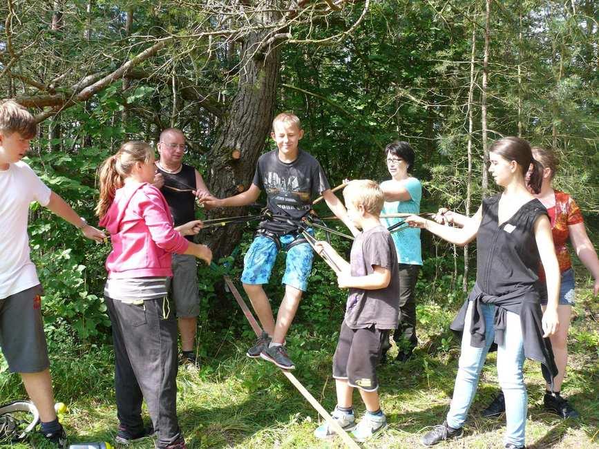 Ein Junge balanciert auf einem etwa 1m hohen Seil im Grünen. Um ihn herum stehen andere Kinder und Erwachsene die ihn abstützen.