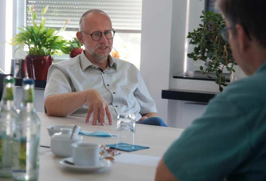 Ein Mann mit Brille und grauem Hemd sitzt an einem Konferenztisch