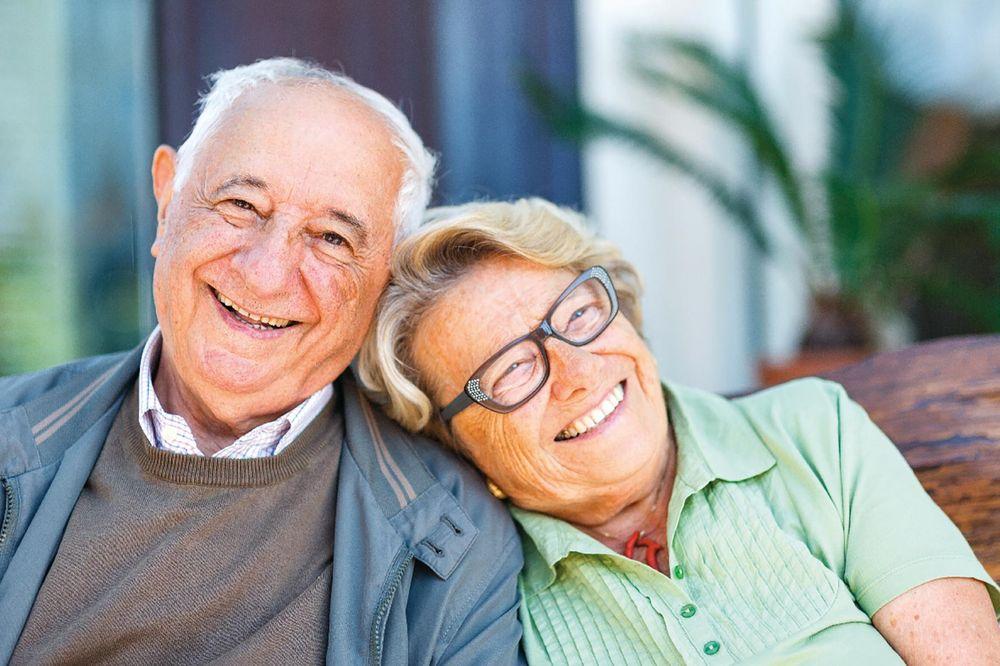 Ein älteres Paar. Sie legt ihren Kopf auf seiner Schulter ab. Beide lächeln.
