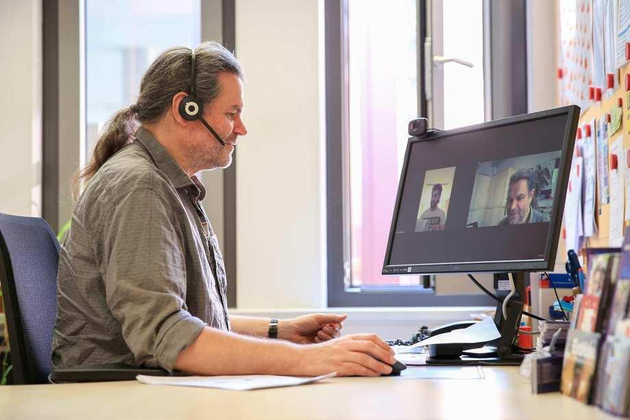 Ein Mann mit Headset sitzt vor einem Computerbildschirm, auf dem ein junger Mann zu sehen ist.