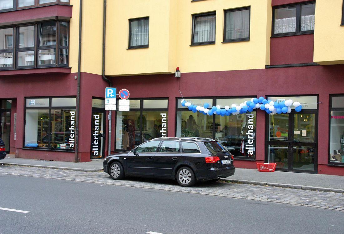 Außenansicht des allerhand-Geschäfts in der Rothenburger Straße. Die Fenster sind mit blauen und weißen Ballons geschmückt. Davor steht ein schwarzes Auto.