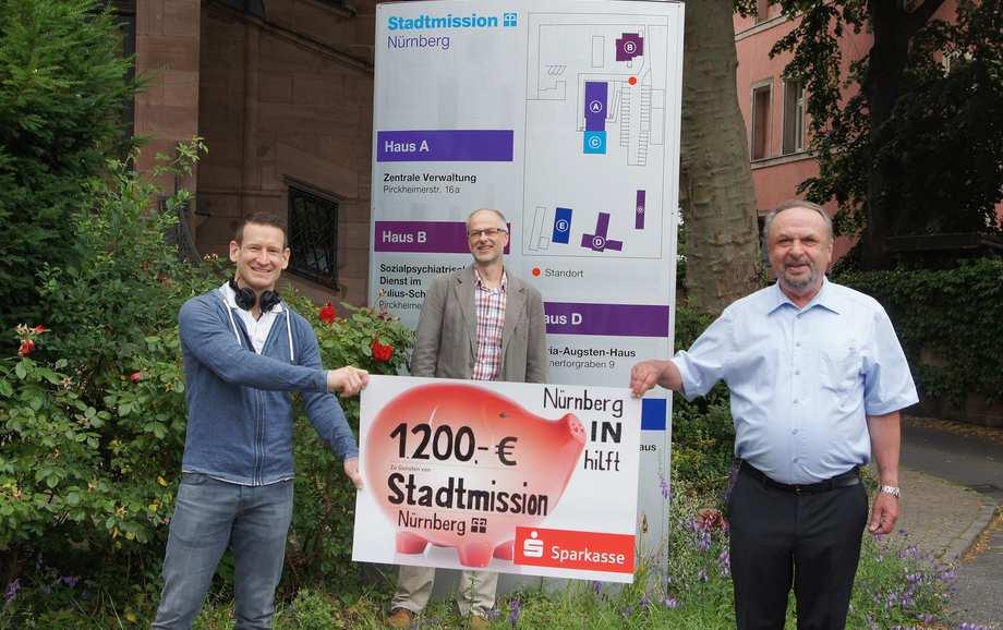 Um einen großen, symbolischen Scheck haben sich Florian Dalferth, Jochen Nußbaum und Dieter Witt mit Abstand positioniert.