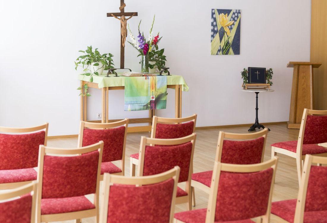Die Kapelle des Christian-Geyer-Heims: Ein heller Raum mit Holzboden und rot bezogenen Stühlen