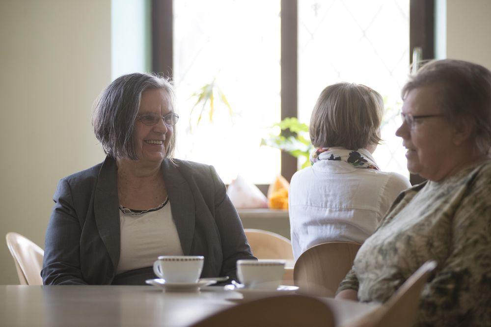 Zwei Frauen, die sich gegenüber sitzen und gemeinsam Kaffee trinken.