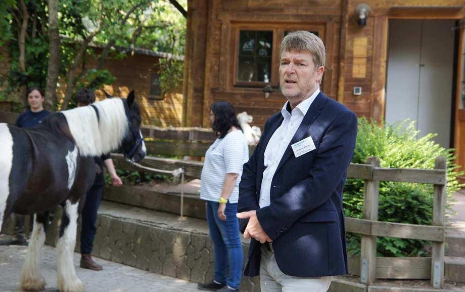 Ein Mann im weißen Hemd und blauen Jackett steht auf einem Hof. Im Hintergrund ein Pferd.