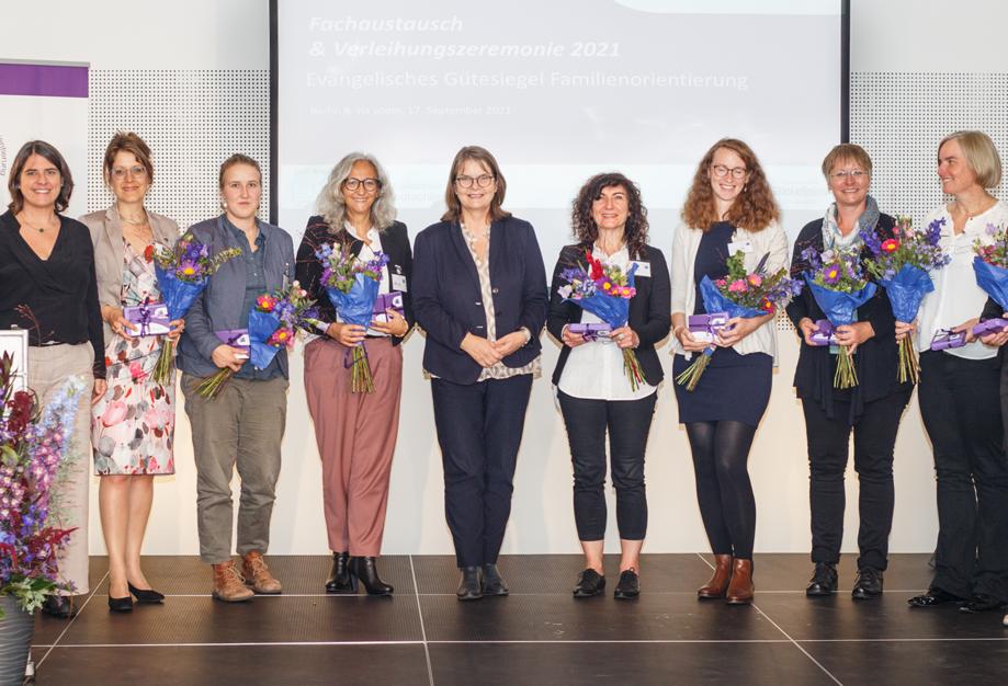 13 Frauen mit Blumensträußen stehen nebeneinander.