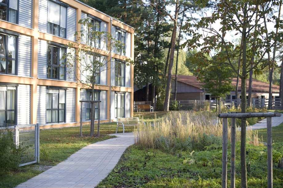 Ein moderner Bau mit großen Glasfenstern in einem grünen Gelände. Ein Weg läuft an dem Gebäude vorbei.