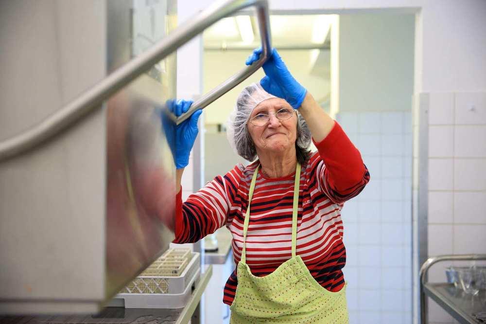 eine Bewohnerin bedient in der Küche Spülmaschine nach dem gemeinsamen Mittagessen
