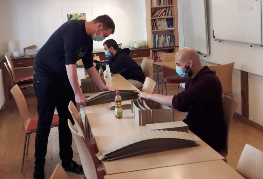 An einem großen Tische sitzen 3 Personen. Sie montieren Kartons.