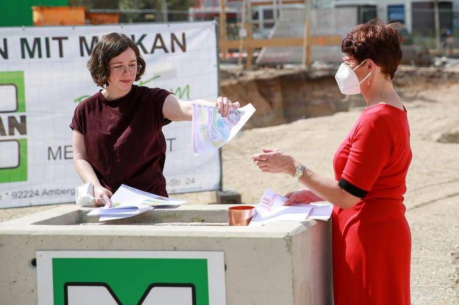 Eine Frau steht auf einer Baustelle. Sie hält Buntstiftzeichnungen hoch.