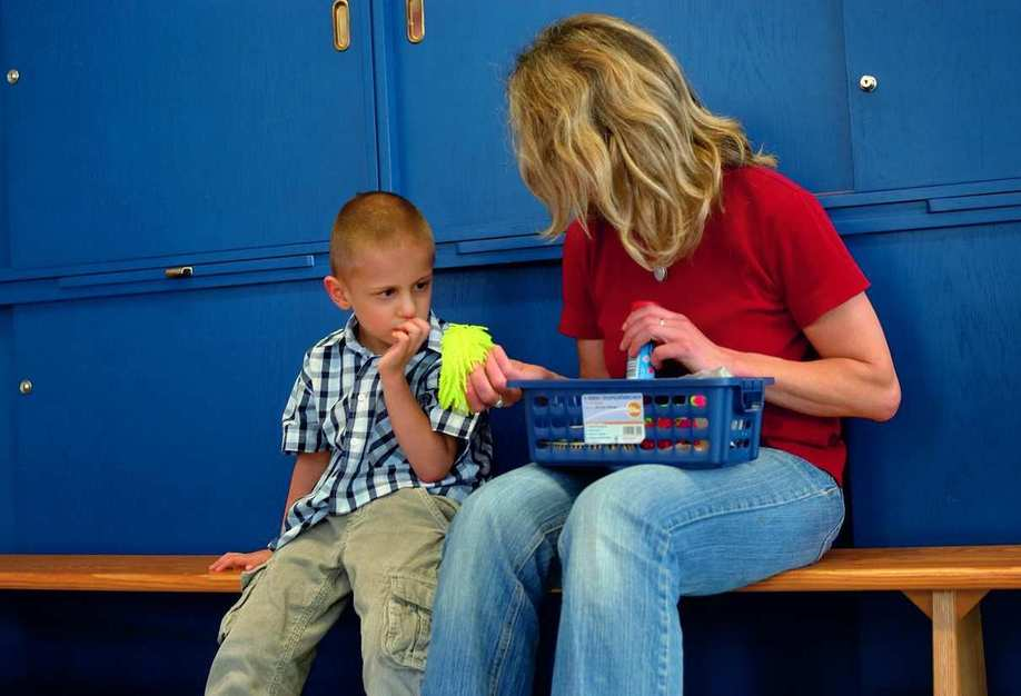 Eine Frau sitzt mit einem Kind auf einer Bank vor blauen Spindschränken
