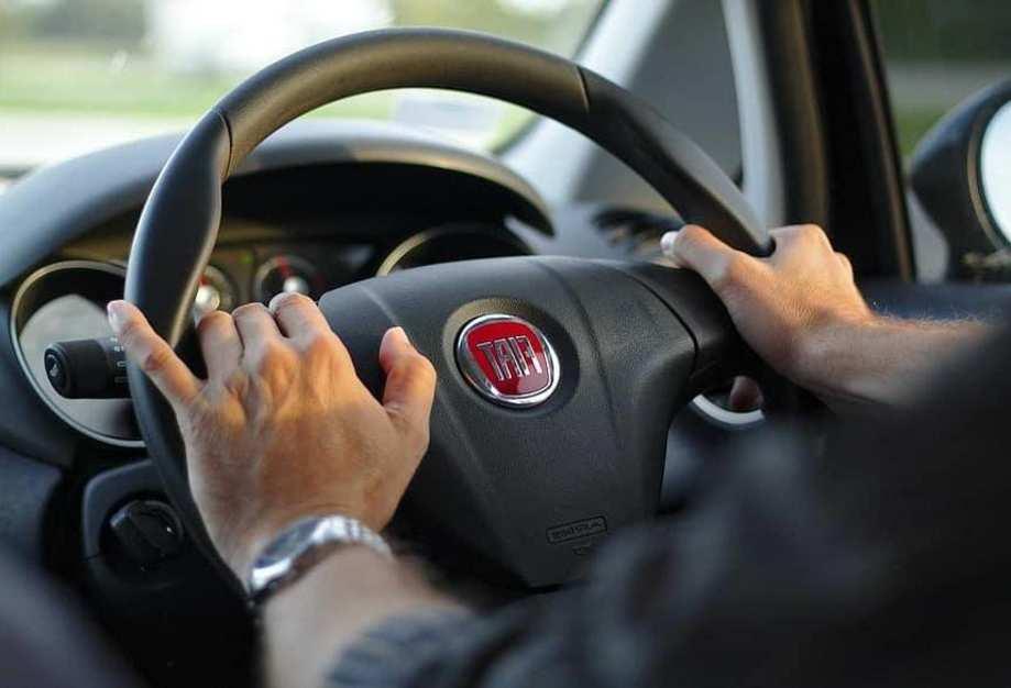 Zwei Hände am Steuer eines Autos.