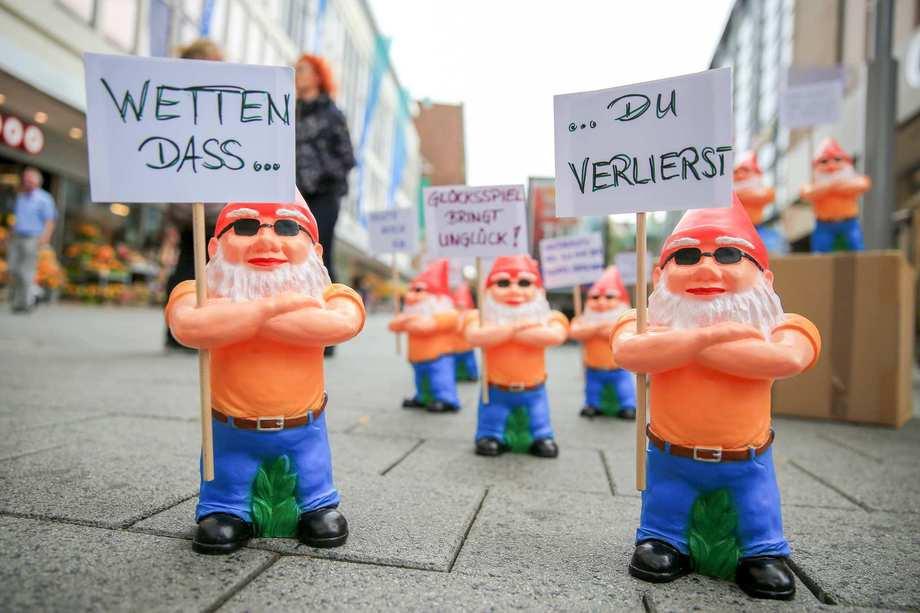 Sechs Zwerge mit orangenen T-Shirts, blauen Hosen und Sonnenbrillen halten Demoschilder hoch. Passanten laufen vorbei.