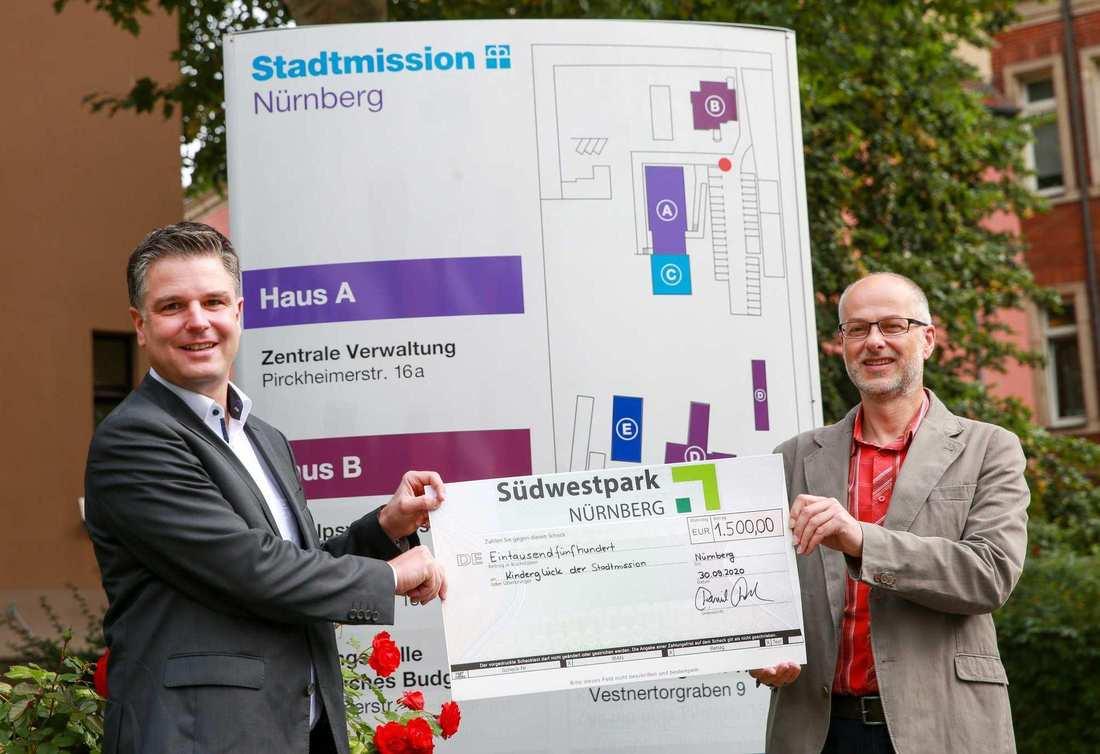 Südwestpark-Geschäftsführer Daniel Pfaller und Jochen Nussbaum, Leiter des Spendenteams der Stadtmission mit dem Scheck im Hof der Stadtmission Nürnberg.