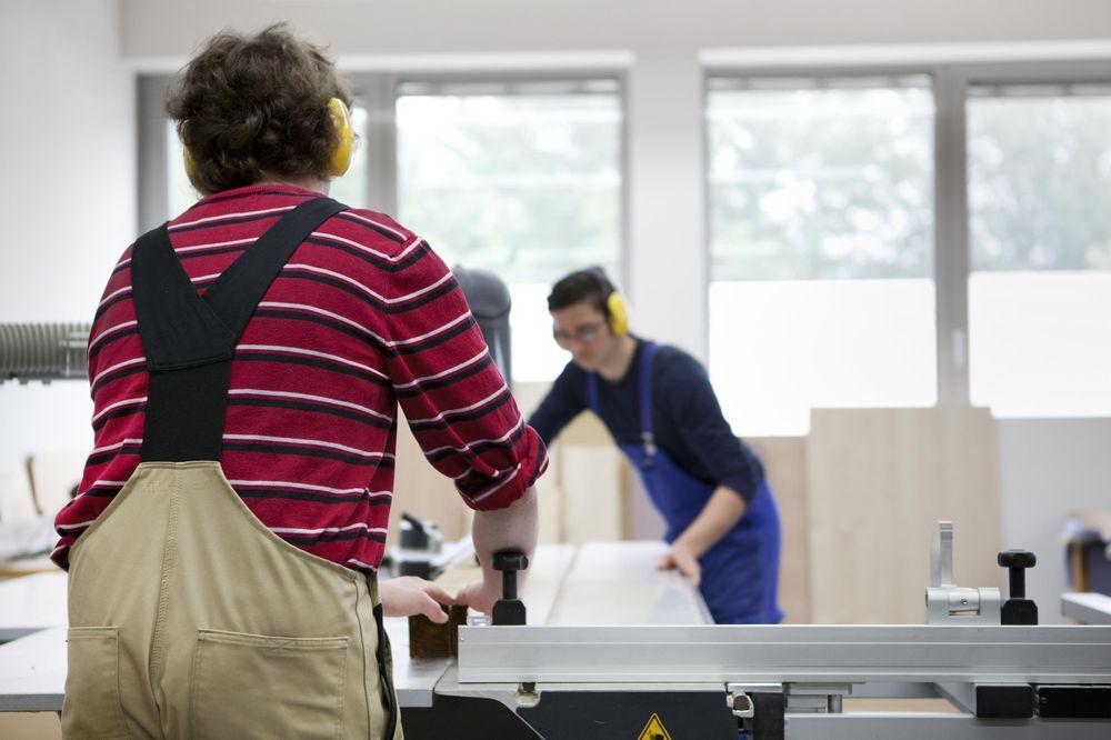 Zwei Männer tätigen mit Gehörschutz Schreinerarbeiten.