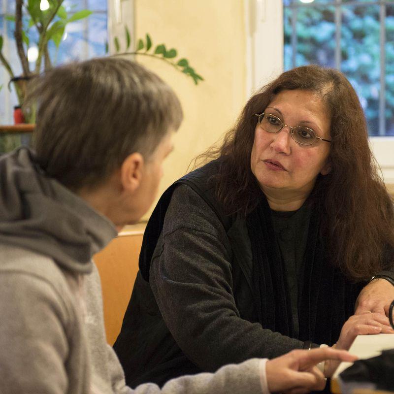 Zwei Frauen sitzen an einem Tisch und unterhalten sich.