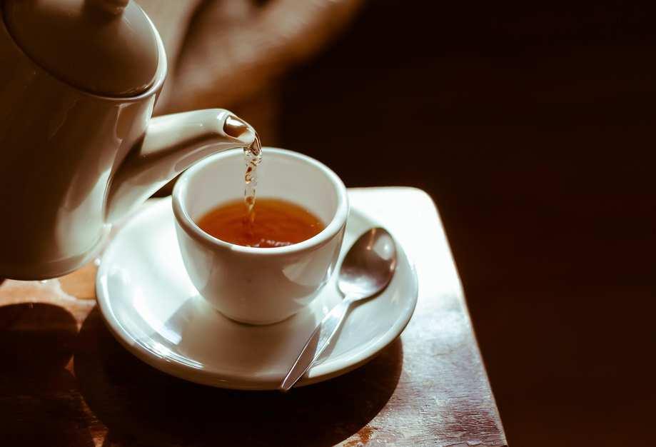 Aus einer Porzellankanne wird Tee in eine weiße Teetasse eingegossen.