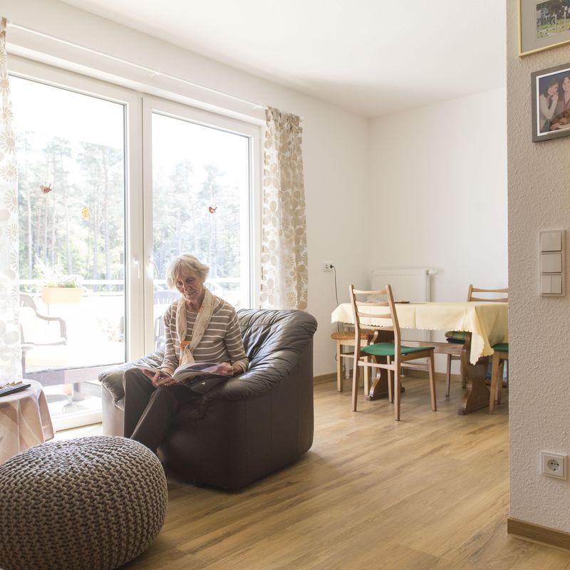 Eine Dame sitzt in ihrem Sessel in Ihrer Wohnung des Betreuten Wohnens.