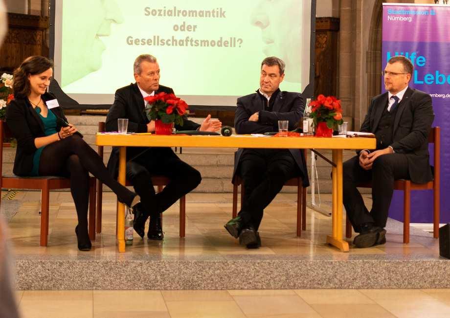 An einem Tisch sitzen Ulrich Maly, Markus Söder. An den beiden Rändern die Moderatoren*innen Sigfried Grillmeyer vom Caritas-Pirckheimer-Haus und Tabea Bozada von der Stadtmission Nürnberg.