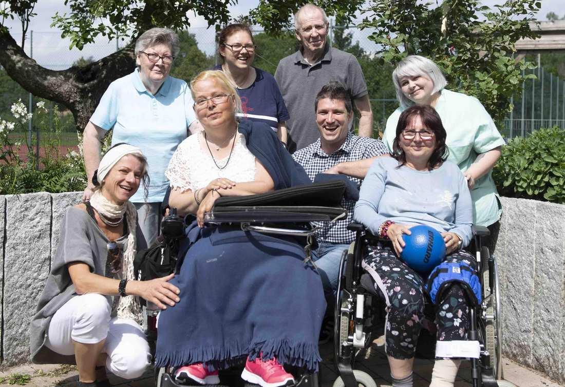 Einige Frauen und Männern gruppieren sich um zwei Rollstuhlfahrerinnen.