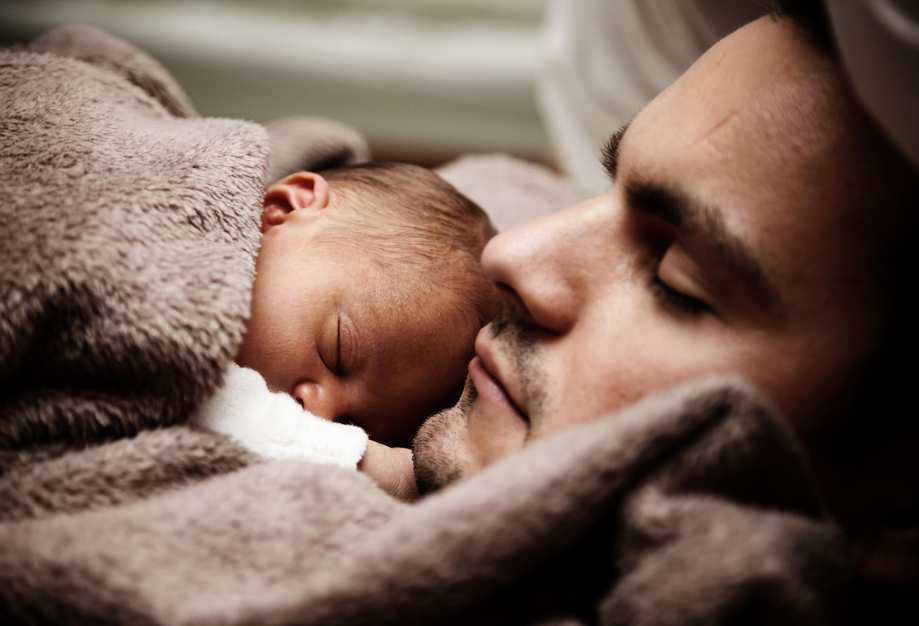 Ein junger Mann hat ein neugeborenes Baby auf der Brust. Beide schlafen.