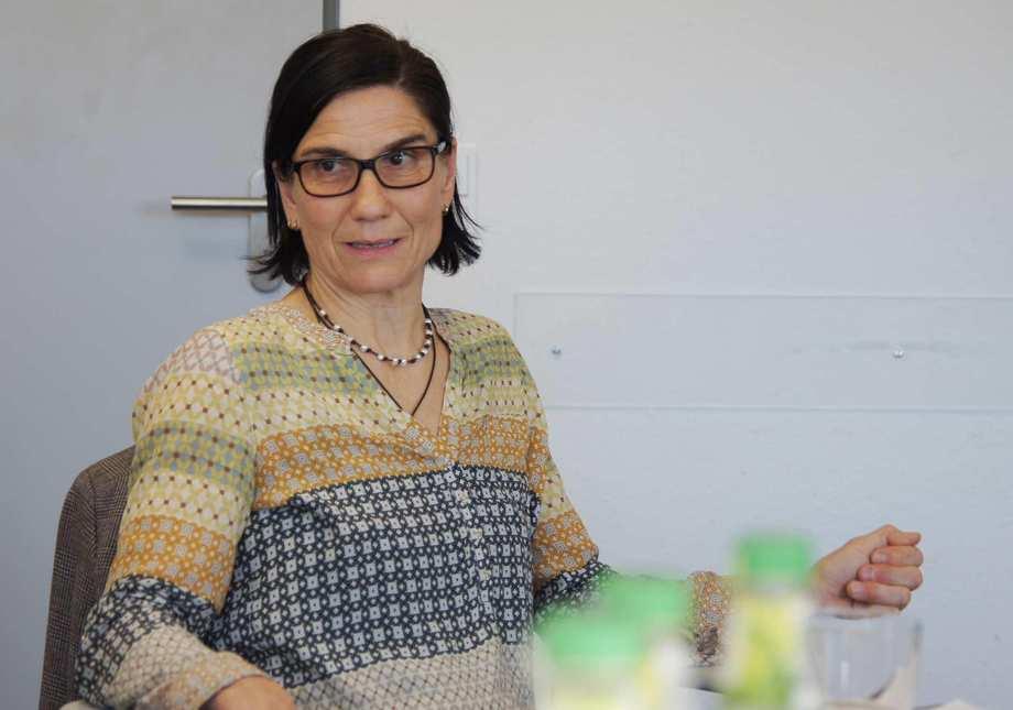 Eine Frau mit schwarzen, halblangen Haaren, Brille und bunter Bluse.