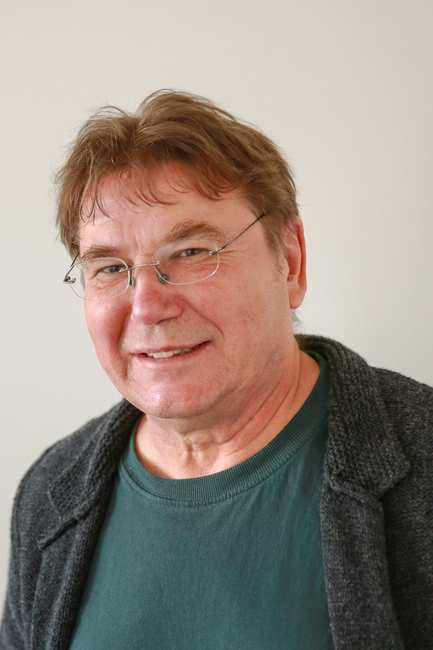 Ein älterer Mann mit Brille un braunem Kurzhaarschnitt
