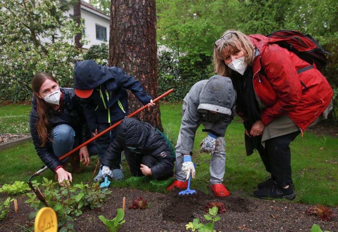 Drei Kinder arbeiten in der Erde. Sie haben Hacken und Harken in der Hand. Neben Ihnen zwei Frauen in Regenjacken.