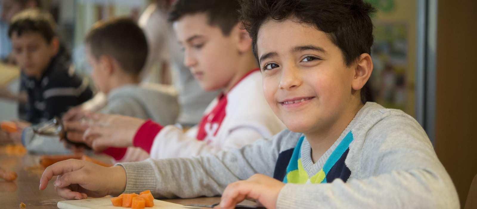 Einige Kinder, die am Tisch sitzen und Gemüse schneiden