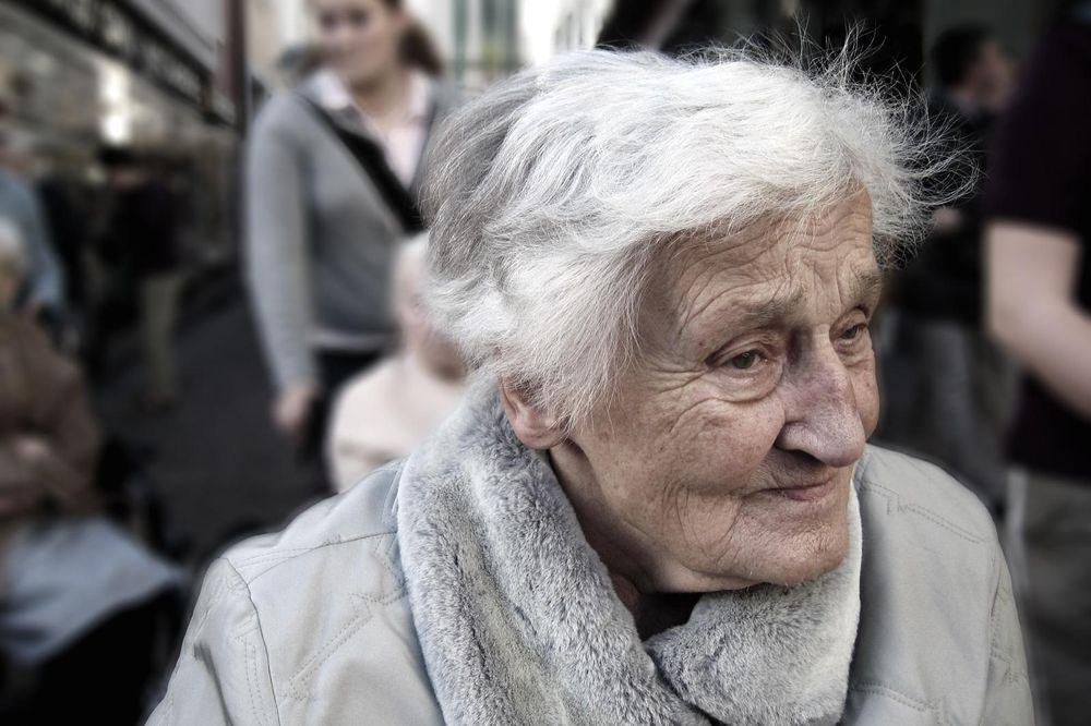 Alte Frau in einem beigen Mantel