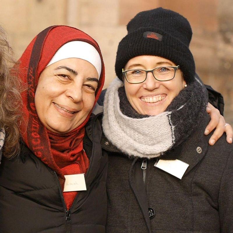 Drei Frauen lachen Arm in Arm in die Kamera.