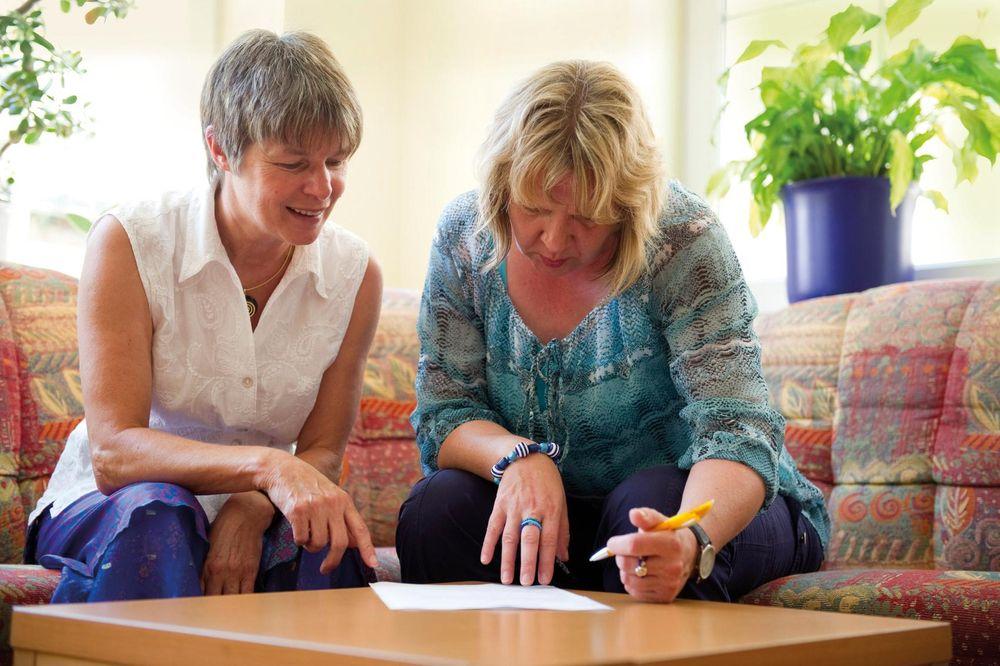 Zwei Frauen sitzen auf der Couch und füllen am Couchtisch ein Formular aus.