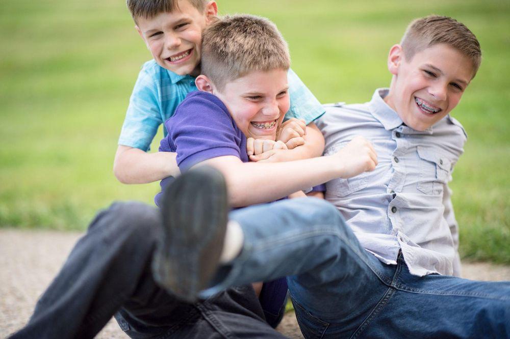Drei blonde Jungen, die am Boden sitzen, lachen und sich drücken