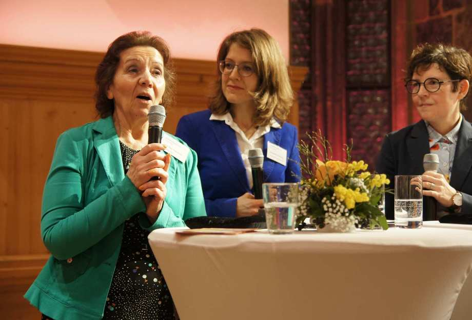 Eine Frau im grünen Blazer spricht ins Mikro. Neben ihr am Stehtisch stehen zwei weitere Frauen und lächeln sie aufmerksam an.