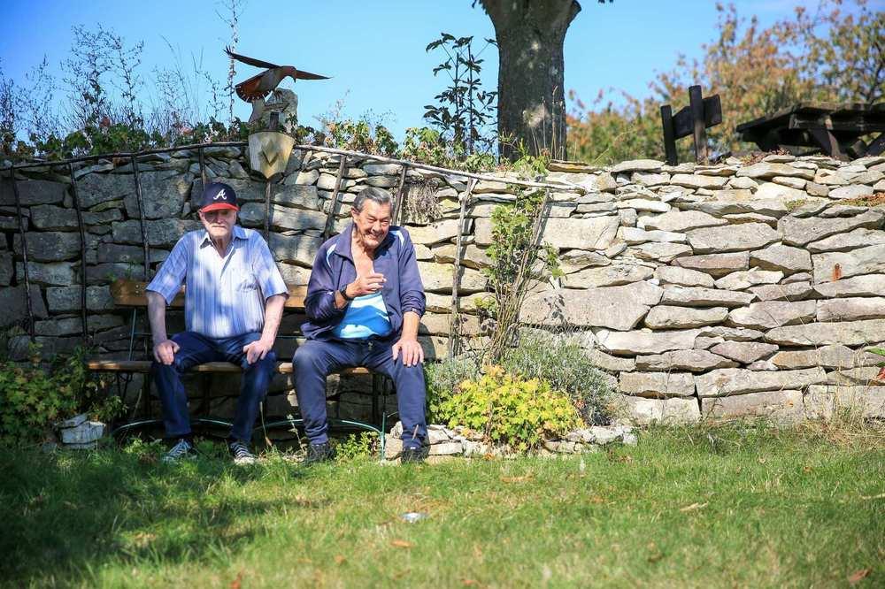 Zwei Bewohner des Haus Martinsruh sitzen auf einer Bank vor einer Bruchsteinmauer
