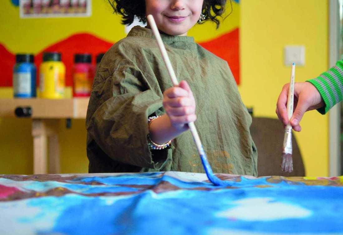 Ein etwa 7 Jahre altes Mädchen mit dunklen Locken steht an einem Maltisch. Sie hat einen großen Pinsel in der Hand.