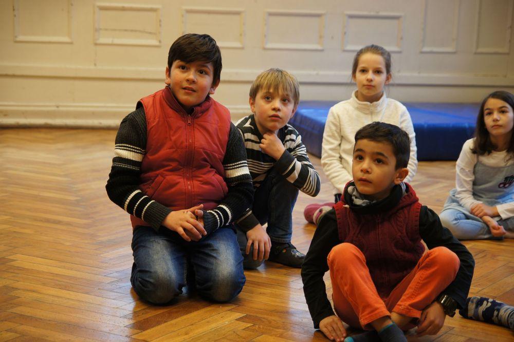 Zwei Mädchen und drei Jungs die am Boden sitzen und etwas beobachten.