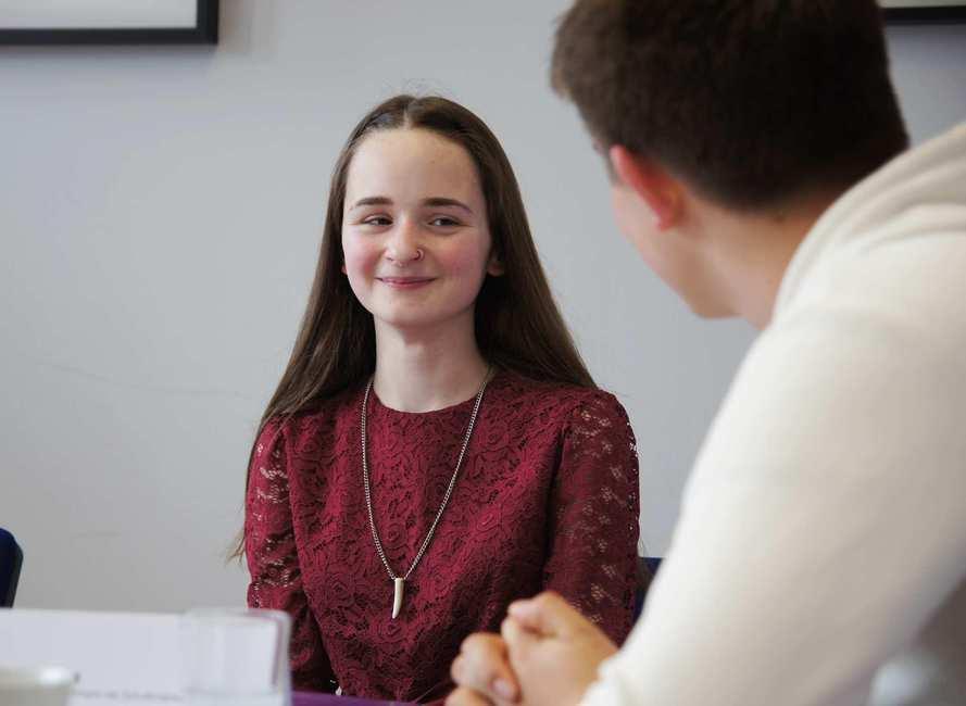 Ein junges Mädchen mit langen braunen Haaren und einem weinroten Kleid.