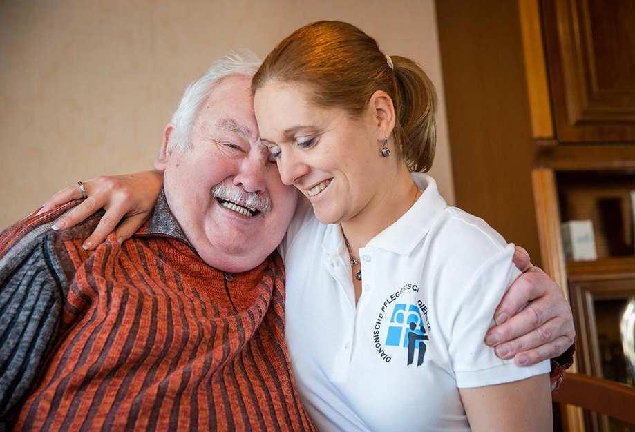 Ein älterer Mann und eine Pflegekraft umarmen sich.