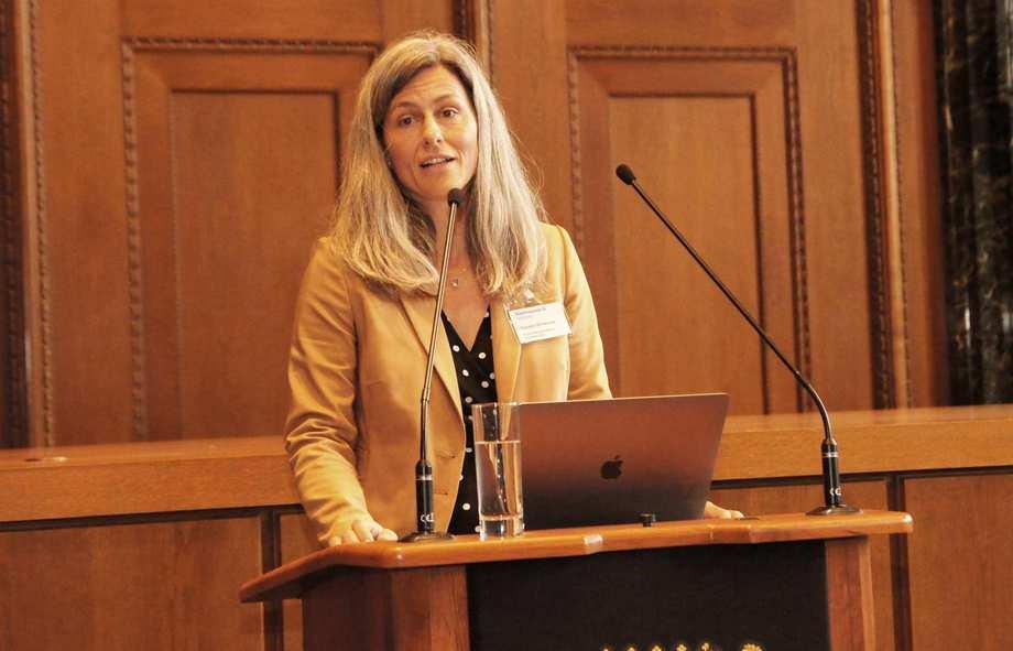 Eine Frau mit grauen langen Haaren und Blazer steht an einem Rednerpult.