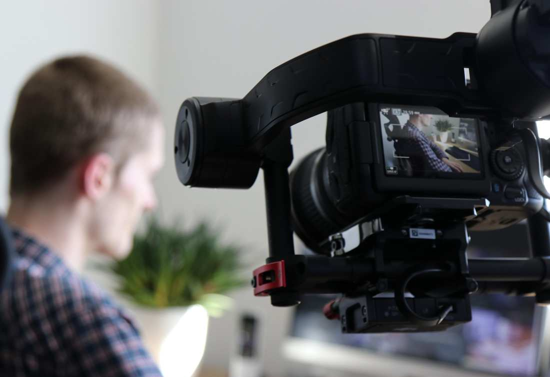 Eine Kamera filmt einen Mann am Schreibtisch.