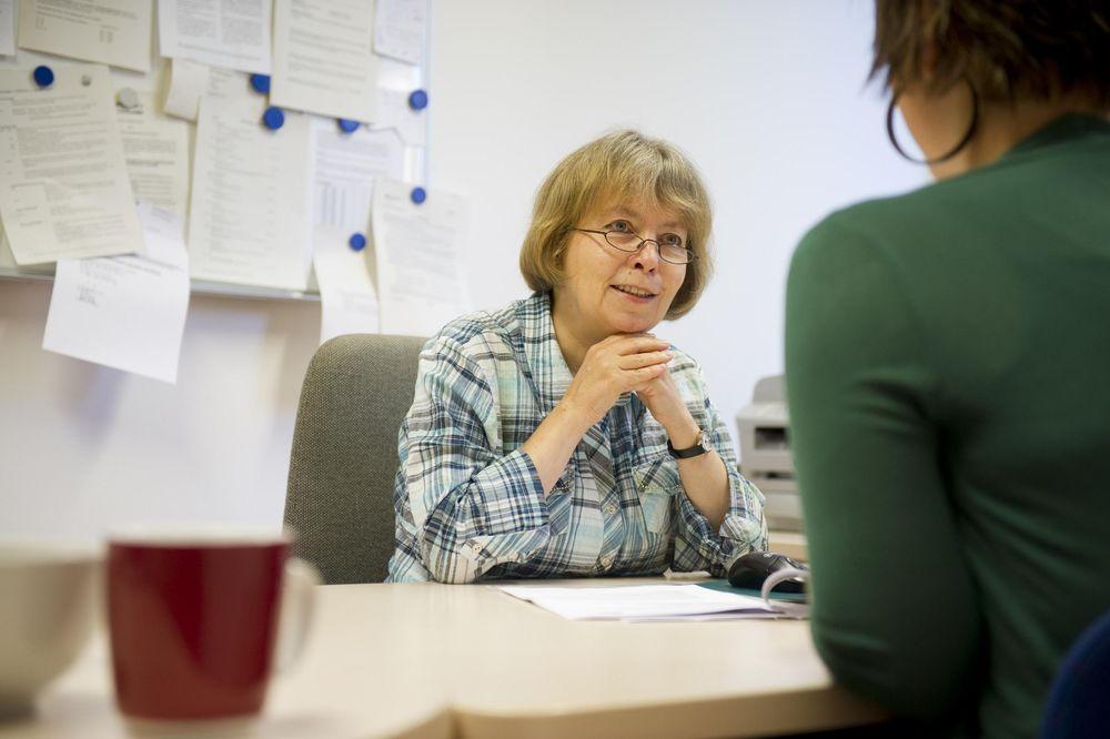 Beratungssituation in einem Büro. Zwei Frauen sitzen sich gegenüber, die eine sieht man nur von hinten.