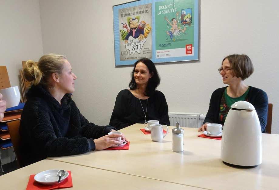 Vier Frauen sitzen an einem Tisch und unterhalten sich bei einer Tasse Kaffee.