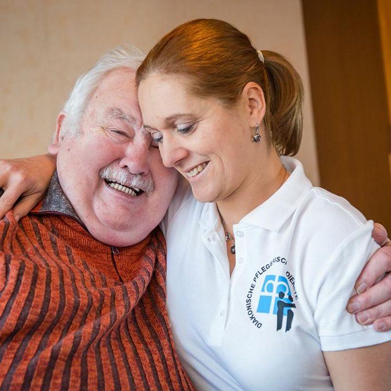 Eine Pflegekraft und ein Senior liegen sich im Arm und lächeln.