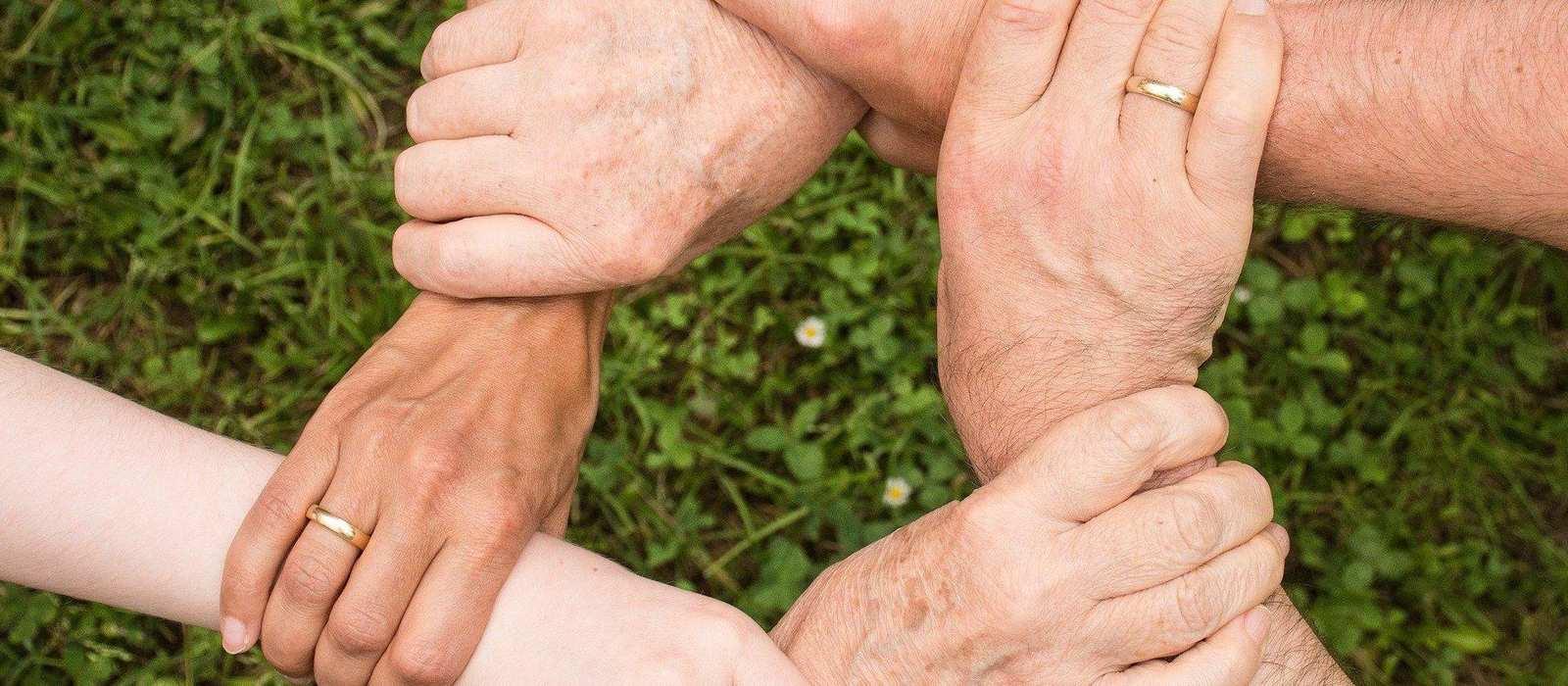 6 Hände halten einander an den Handgelenken und bilden dabei einen Kreis.