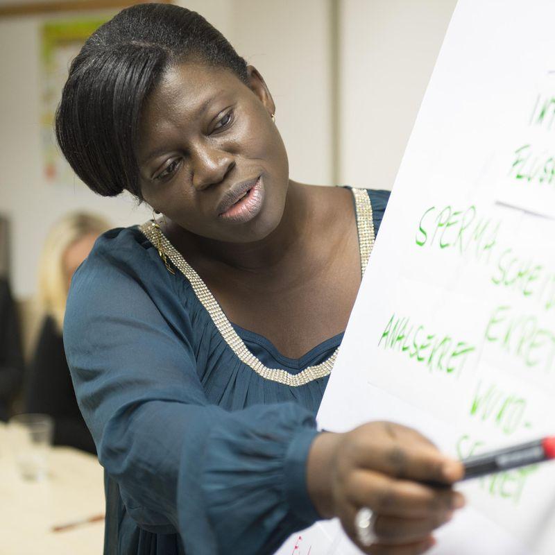 Eine Frau steht neben einem Flip-Chart und erklärt die darauf stehenden Begriffe.