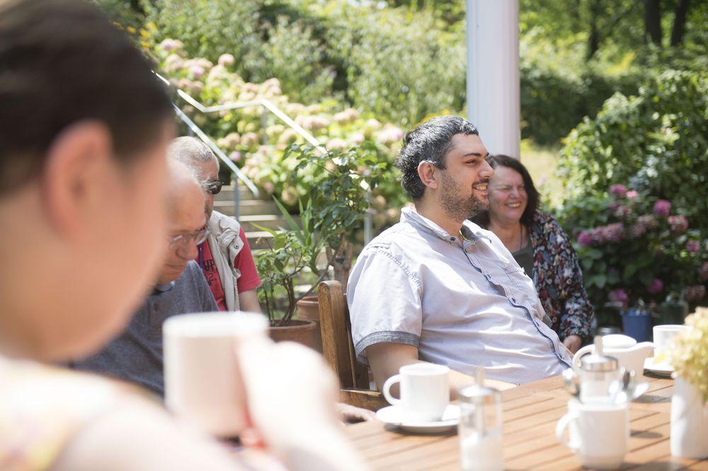 Personen sitzen um einen Tisch im Garten und trinken Kaffee.