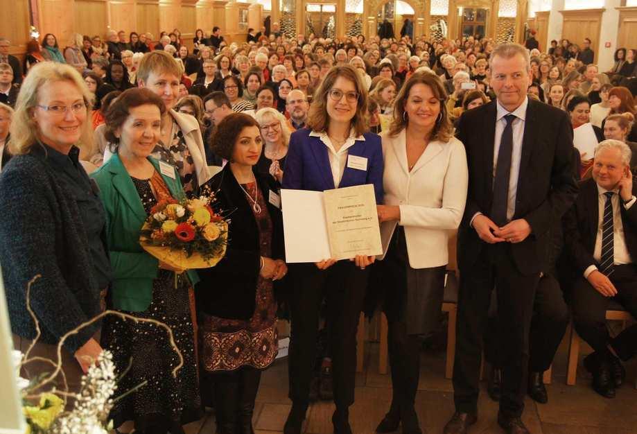 Oberbrügermeister Ulrich Maly steht neben sechs Frauen. Hinter ihnen der vollbesetzte Rathaussaal.